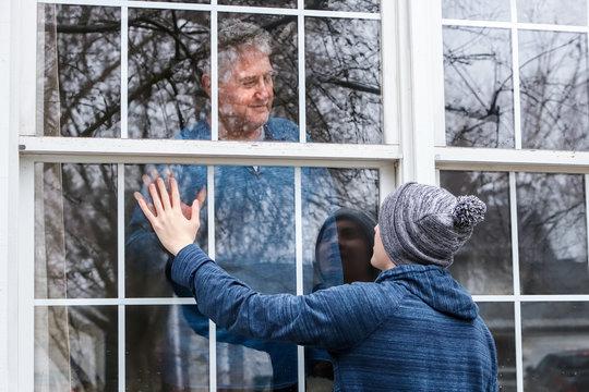 Teen visiting senior citzen quarantined in home, touching hands through the window