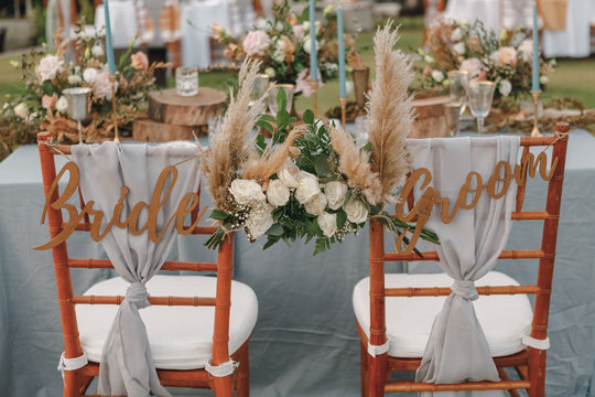 Two chairs assigned to the bride and groom at a wedding setting. Bride and groom. Wedding bride and groom Signs on chairs standing in the woods.