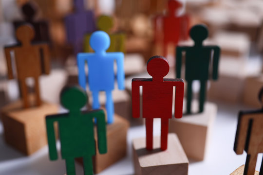 Colored wooden figures in form man stand table. Desire to perform tasks that are prescribed in job description. Satisfy inner desires and ambitions. Need for membership in social group
