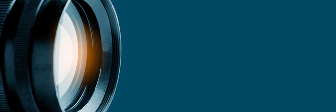 Photo or video camera lens on a blue background. Panoramic image, soft focus. The concept of news, media information