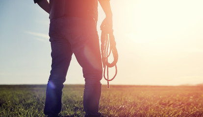 A man cowboy hat and a loso in the field. American farmer in a field wearing a jeans hat and with a loso. A man is walking across the field silhouette Wall mural