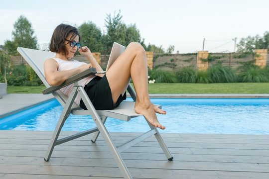 Mature woman sitting in chair near private pool with laptop, female working at home