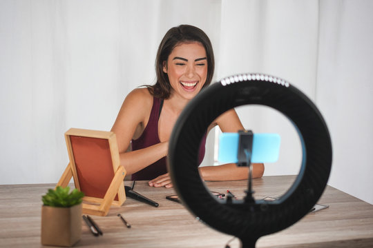 Young influencer woman creating social media videos with smartphone camera while putting on make up - New digital jobs trends, technology, cosmetics and fashion concept - Focus on her face