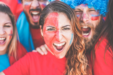 Crazy sport fans screaming while supporting their team - Football people supporters with painted faces having fun inside stadium for soccer match - Event and bet concept - Focus on girl eyes