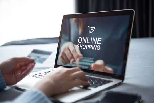 E-commerce and online shopping concept, Woman hand using laptop (Mockup website) and holding credit card for shopping payment online at home.