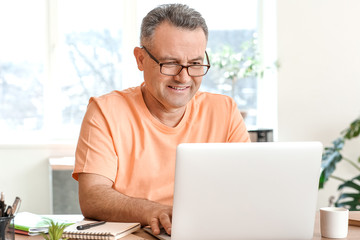 Spoed Fotobehang Wanddecoratie met eigen foto Mature man using laptop at home