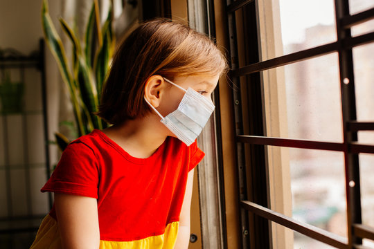 Small child with virus protection surgical face mask looking out the window, staying home for social distancing due to coronavirus