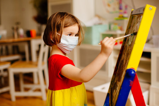 Portrait of a small preschool child with face mask against coronavirus, painting at an art easel at home
