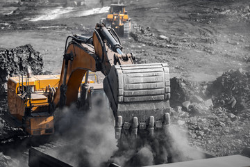Excavator work loading of coal into Yellow mining truck. Open pit mine industry Fototapete