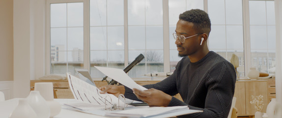 Handsome African American male working from home, using laptop in living room, checking documents Wall mural