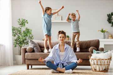Happy mother with closed eyes meditating in lotus pose on floor trying to save inner harmony while excited children jumping on sofa and screaming in light spacious living room.