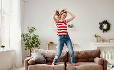 Happy woman listening to music and dancing on couch at home.