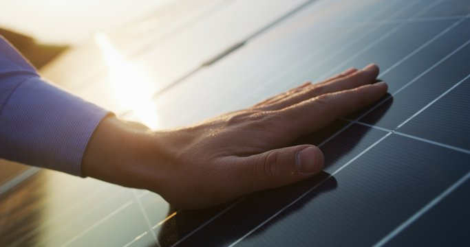 Close up of an young engineer hand is checking an operation of sun and cleanliness of photovoltaic solar panels on a sunset.Concept:renewable energy, technology,electricity,service, green,future