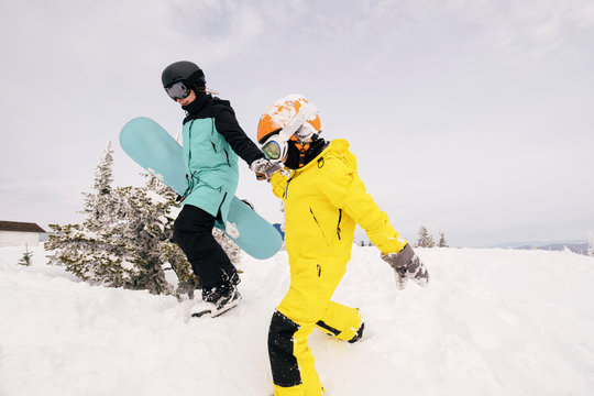 Family of snowboarders mother and kid playing and have fun in snow on mountain top. Sunny holiday in ski resort