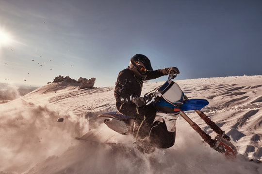 Snowbike rider in mountain valley. Modify dirt bike with snow splashes and trail. Snowmobile sport riding, winter sunny day