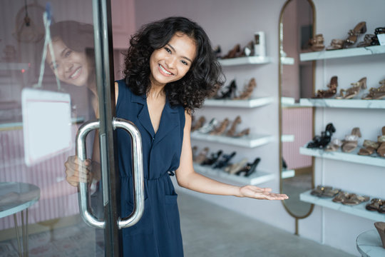 beautiful young asian fashion shop owner at her boutique standing proudly welcoming customer open the front door