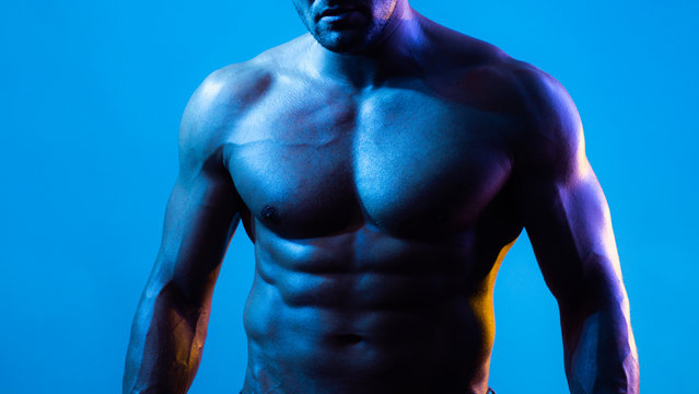 Muscular model sports young man on blue dark background. Fashion portrait of strong brutal guy with a modern trendy blue color. Sexy bare torso. Sport workout bodybuilding concep.