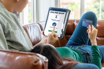 Young couple use credit card for online shopping on internet website at home. Number on the credit card is mock up. No personal information shown on the credit card. Online business shopping concept.