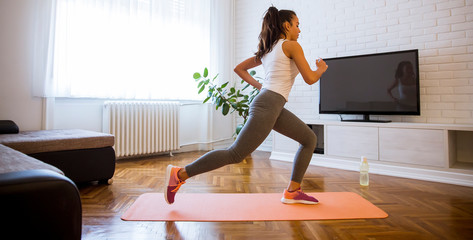 Young attractive woman practicing exercises at home Fotomurales
