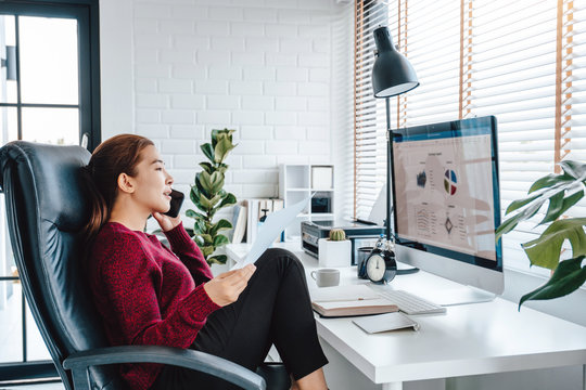 Asian woman working from home using computer and drinking coffee in her bedroom document finance and conference online meeting for new projects