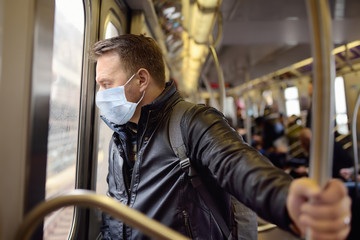 Mature man wearing disposable medical face mask in car of the subway in New York during coronavirus outbreak. Fototapete