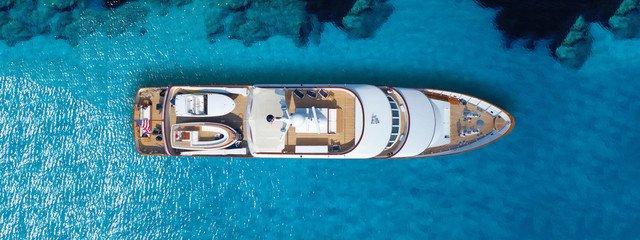 Aerial drone top down ultra wide photo of luxury yacht anchored in tropical exotic island turquoise sea