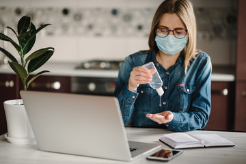 Coronavirus. Sanitizer gel. Business woman working, wearing protective mask in quarantine. Cleaning hands antibacterial gel to eliminate germs. Stay at home. Girl learns, using laptop. Freelance. Fototapete
