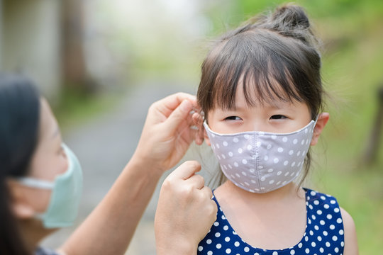 Mother is wearing a cloth mask for little girl protect herself from Coronavirus when child leave the house mom is wearing mask on her nose for safety outdoor activity,illness or Air pollution