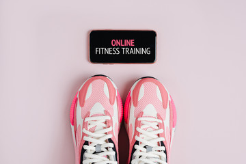 New sneakers and smartphone on a pink background. App for training indoors. Online Fitness program. Home online workout. Top view, flat lay