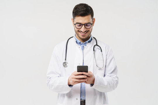 Young male doctor in white coat smiling while looking at screen of his phone, using medical app, standing isolated on gray background
