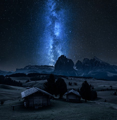 Wall Mural - Milky way over wooden huts in Alpe di Siusi, Dolomites