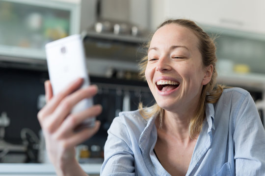 Young smiling cheerful woman indoors at home kitchen using social media apps on phone for video chatting and stying connected with her loved ones. Stay at home, social distancing lifestyle.