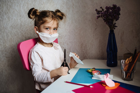 Five year old girl in medical mask is engaged in creative work. Protective mask with their own hands. What to do to quarantine a child. Homeschooling during quarantine. Stay at home entertainment.