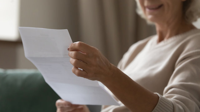 Close up wrinkled female hands holding paper document. Smiling happy middle aged senior woman reading letter, feeling excited by good news, final banking loan credit mortgage payment notification.