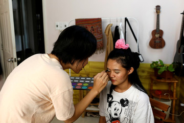 Nhu (L), 23, and Thanh, 21, put on make up to take pictures for their Instagram and Tik Tok pages as they stay home during the outbreak of the coronavirus diease (COVID-19), in Ho Chi Minh