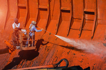 Washing and cleaning, worker High pressure water jet to cleaning with Old ship washing wearing safety harness with in side cargo hold under ship repair in floating dry dock in shipyard