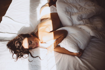 Beautiful young girl in the morning in a white bed after waking up joyful smiling at a new day and the sun out of the window hugging a pillow. Soft selective focus. Toned photo. Fotomurales