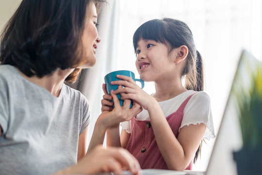Asian young office mother work from home during coranavirus outbreak. Cute daughter give a cup of coffee to mom and kiss for a break and rest. Love care in family. Covid-19, Social distancing concept