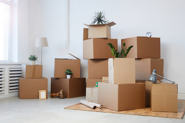 Minimal background image of cardboard boxes stacked in empty room with plants and personal belongings inside, moving or relocation concept, copy space