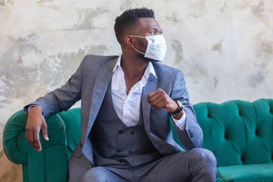 COVID-19. Confident young African man is wearing a protective medical face mask to prevent infection with coronavirus and pandemic sitting on a green sofa in a grey suit against a concrete wall