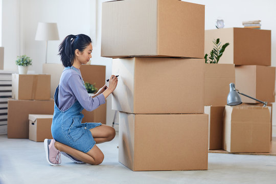 Side view full length portrait of young Asian woman writing on cardboard boxes labeling them for moving out, copy space