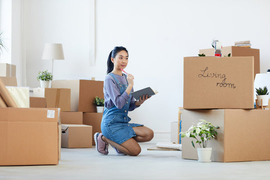 Full length portrait of young Asian woman organizing moving in process while sitting on floor next to cardboard boxes and holding planner, copy space