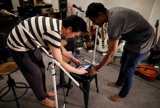 Musicians Jack and Rai set up their iPad as they prepare to perform for their fans on Instagram Live in Singapore