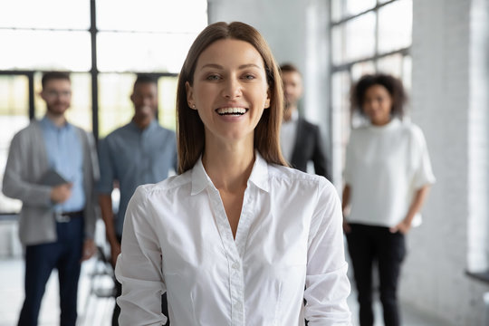 Close up headshot portrait of happy laughing attractive businesswoman looking at camera. Different smiling businesspeople standing behind of female business hr. Leader of multi-ethnic team concept.