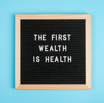 The first wealth is health. Motivational quote on black letter board on blue background. Concept Health Care and Medicine, inspirational quote of the day