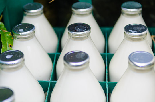 Traditional foil capped milk bottles in a crate.