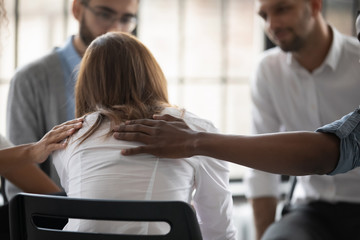 Close up back view unhappy woman with supporting diverse people at therapy session, touching...