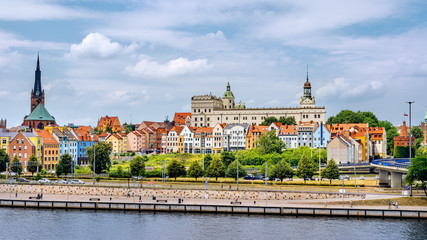 People walking on Piastowski Boulevard. Old town, Castle of Pomeranian Dukes and Cathedral Basilica of St James the Apostle in background, Szczecin