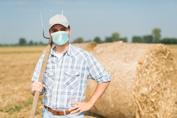 Farmer in his field while wearing a mask, coronavirus pandemic concept Fotomurales