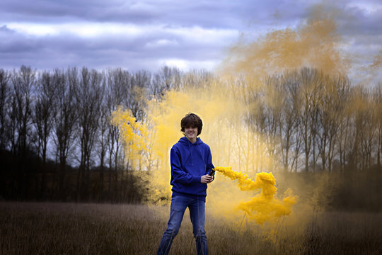 Teenager boy in the woods playing with yellow smoke bomb